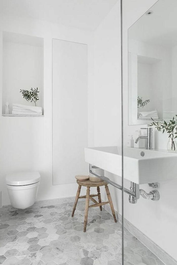 decoracion en blanco y gris, suelo con baldosas hexagonales, espejo grande, taburete de madera rustico, baños pequeños con ducha, ramas con hojas verdes