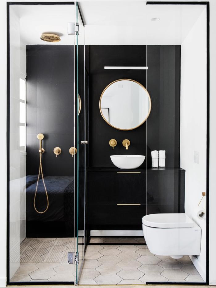 cuartos de baño pequeños, decoración moderna con pared de acento en negro, espejo redondo, mini lavabo, metal color dorado