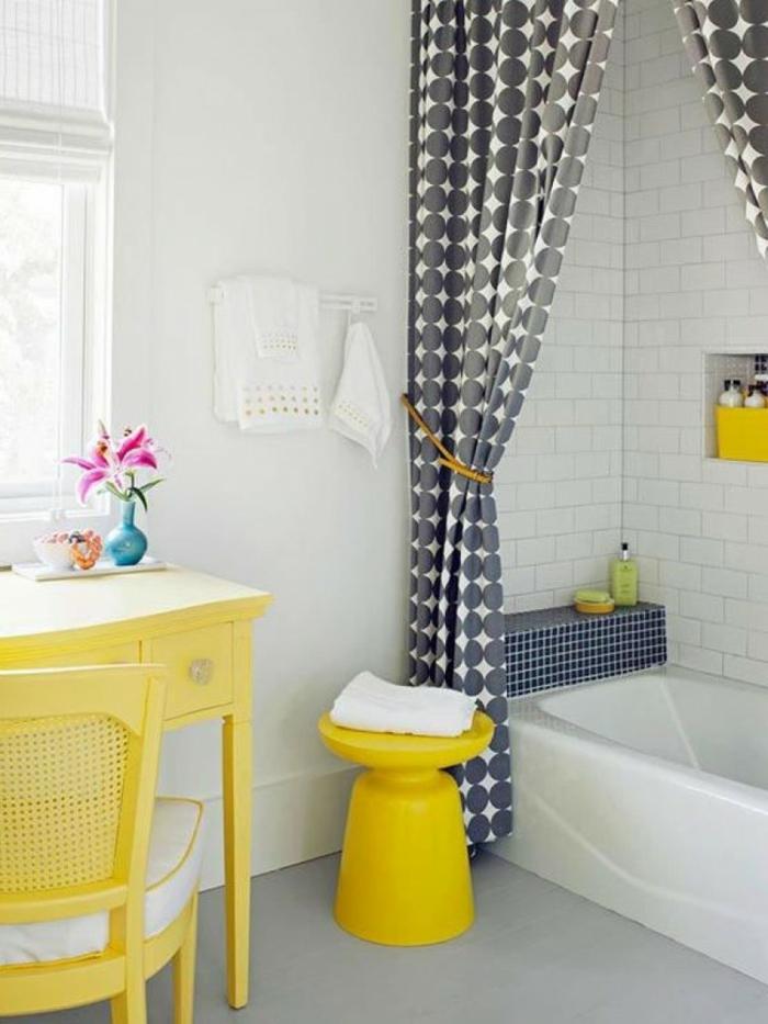 baño en gris y amarillo limon, ducha y bañera, cortina en círculos, mesa de madera y silla tapizada, baños pequeños con ducha, mucha luz natural,