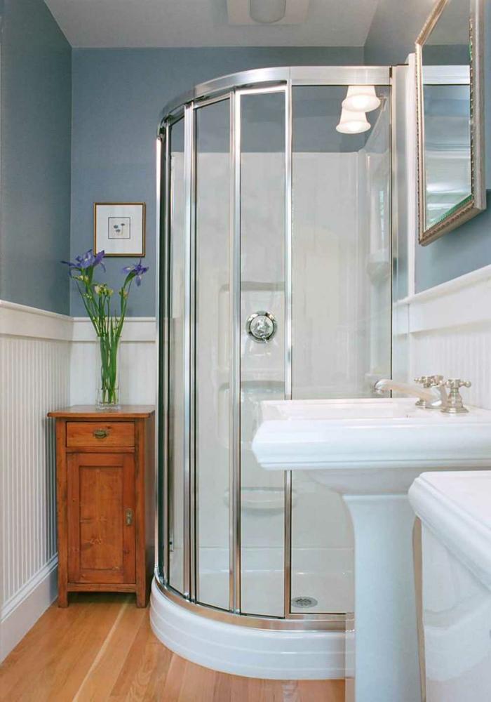 cabina de ducha con marcos de metal, suelo laminado, armario pequeño con flores, paredes en azul y blanco, espejo rectangular, decoracion baños pequeños