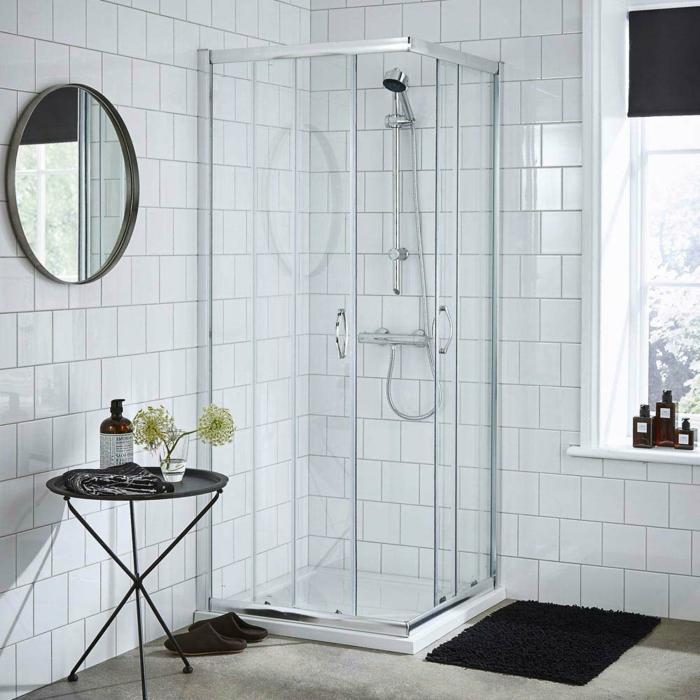 baño moderno con cabina de ducha en el angulo, ventana grande, cuartos de baño, espejo redondo, mesita redonda negra