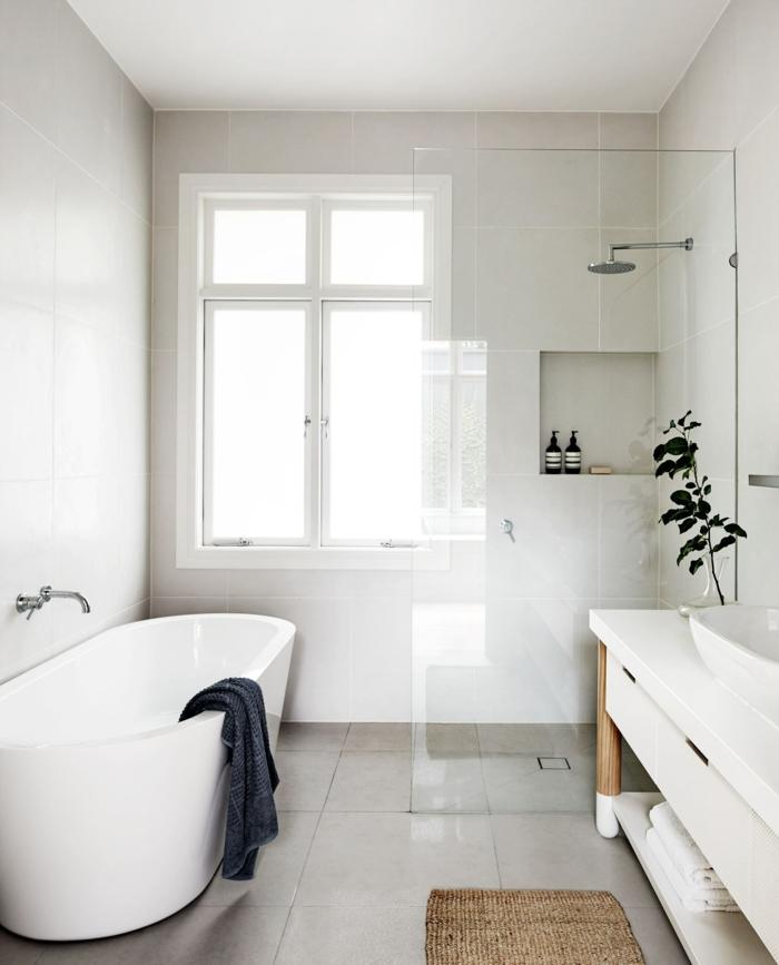 baño lujoso pequeño con ducha y bañera, suelo con baldosas, mueble lavabo grande, pared con nichos, ventanas grandes, tapète de mimbre
