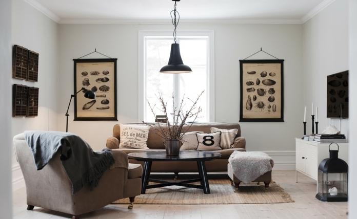 decoracion estilo nordico, sala de estar en marrón y negro, paredes decoradas con fotos de especies biológicas, lámpara colgante, mesa negra redonda de madera, sillón con patas, portavelas y televisor