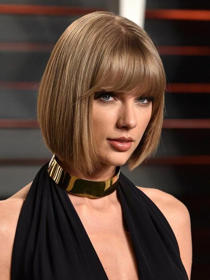 Tylor Swift con bob lacio, flequillo largo denso curvado, cortes con flequillo, blusa negra, collar dorado