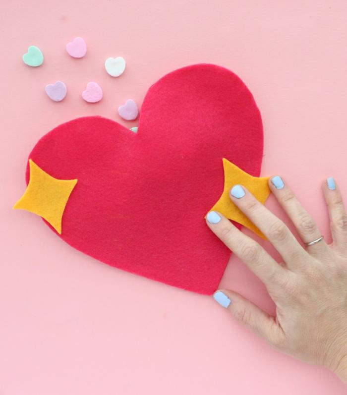 manualidades de fieltro para el día de san valentín, bolsa DIY en forma de corazón llena de caramelos en colores pastel