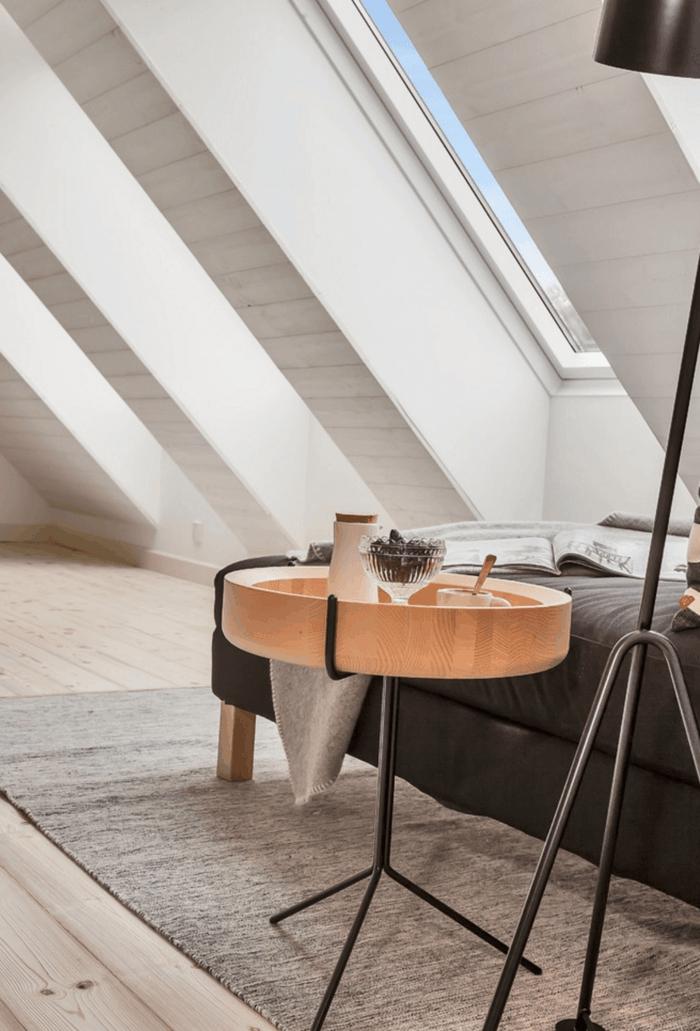 habitacion con techo inclinado y mucha luz, dormitorio nordico, cama gris, mesita original de amdera, suelo con tarima, paredes de listones, alfombra gris
