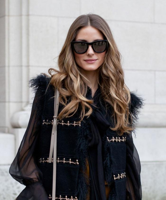 apariencia moderna con atuendo en negro y larga caballera en rubio oscuro con mechas rubias