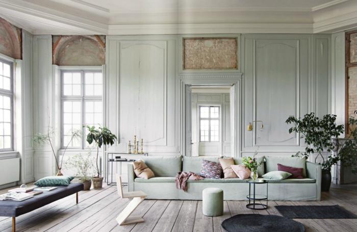 estilo nordico, casa antigua con techos altos y paredes de madera, azul pálido, suelo con tarima, sofá grande con cojines colores pastel, árboles decorativos, ventanas gramdes, banco tapizado, mini mesa