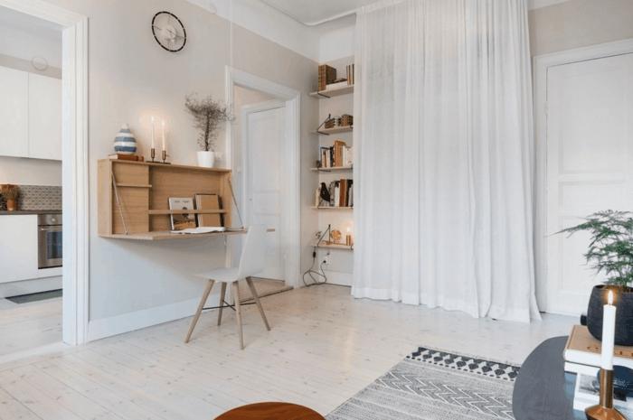 estilo nórdico, salón funcional con escritorio plegable de madera, estantería con cortina blanca ligera, suelo con tarima, tapete gris con figuras geométricasreloj de pared, vela encendida