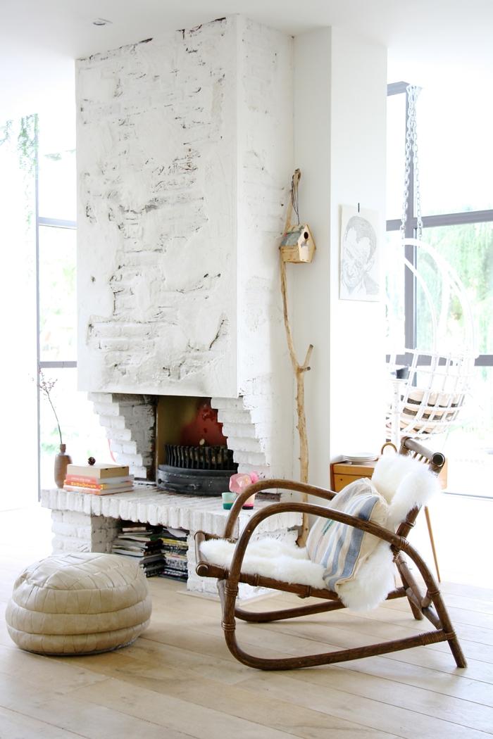 decoracion estilo nordico, salón con luz natural, chimenea de obra con ladrillo visto, pintura blanca, sillón de bambú con cojín, puf de cuero, casa para pájaros