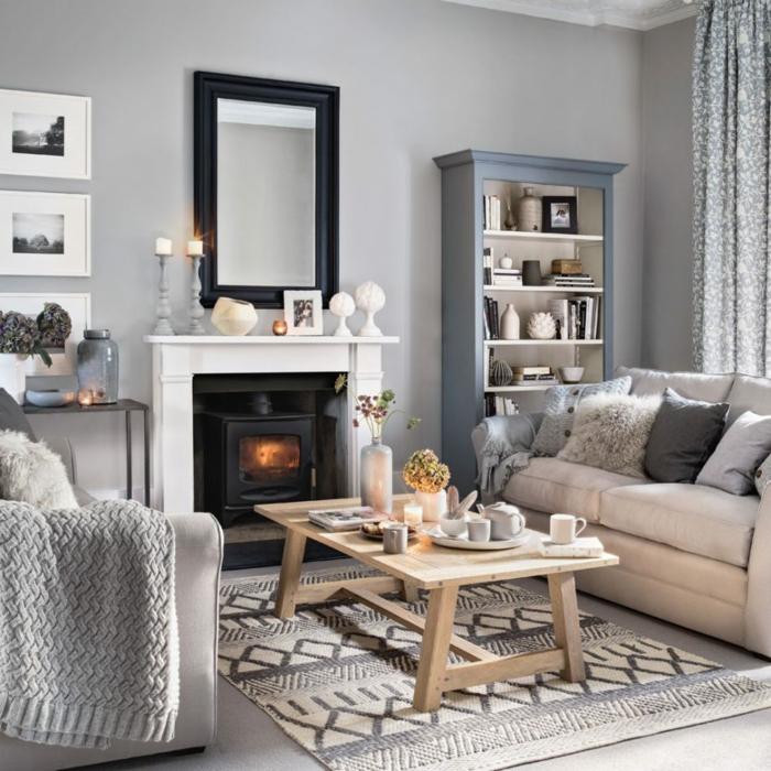 salon epqueño con encanto, chimenea encendida, mesa de madera, suelo laminado, alfombra tejida, espejo con marco negro, habitación gris, sofá con cojines, fotografia blanco y negro, libreria
