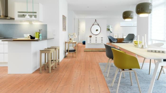 espacio grande, cocina abierta al salón, mesa grande con sillas de plástico en gris y color oliva, tapete azul, sillas de barra, espejo en la pared, casas nordicas