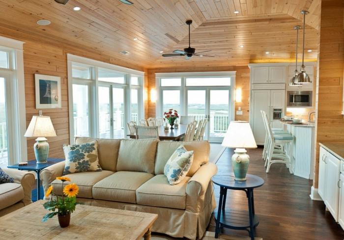 ideas de cocinas abiertas al comedor y al salon, techo y paredes revestidos de parquet, sofa en beige y cojines decorativos con motivos florales