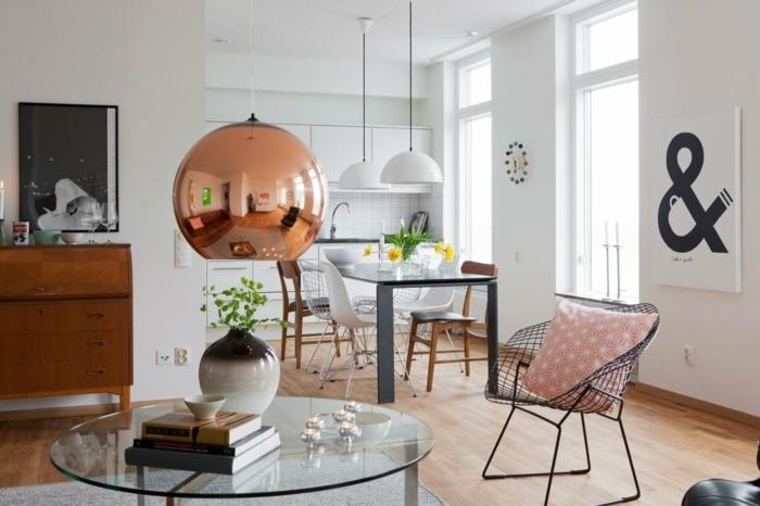 salon comedor, estilo nordico, mesa grande con sillas desparejas, mesita baja de vidrio, silla con huecos y cojin rosado, lámpara colgante grande color cobrizo, paredes blancas, flores