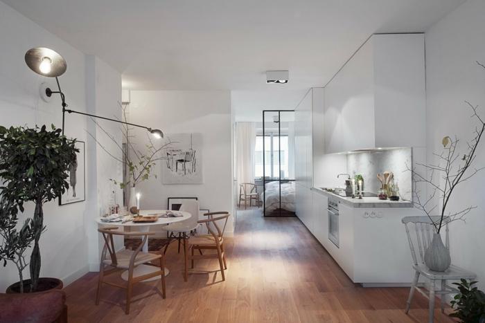 comedor separado de dormitorio con separador de vidrio, cocina blanca, mesa redonda con sillas de madera, suelo laminado, árbol decorativo, salon nordico