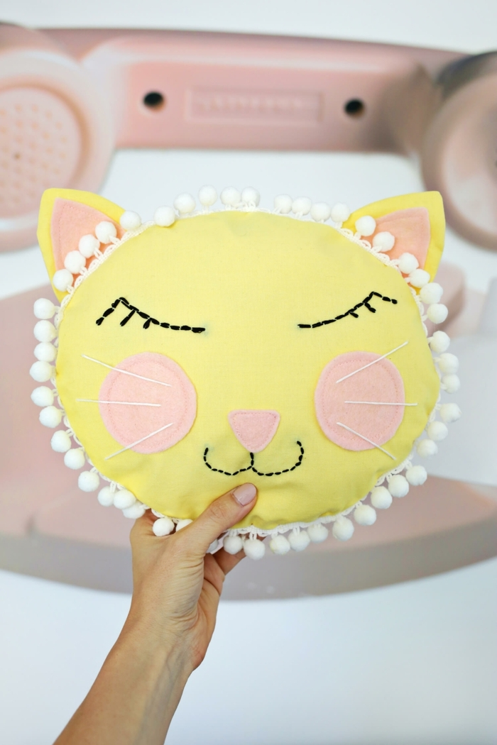 cara de gato hecha de fieltro en amarillo y rosado, manualidades con tela ideas originales, almohada decorativa en forma de gato