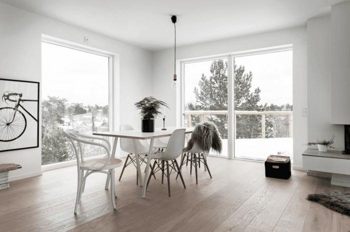 salón moderno, estilo nórdico, decoración en blanco y negro, cuadro grande con bicicleta, mesa rectangular, sillas de madera y plástico., terraza con nieve