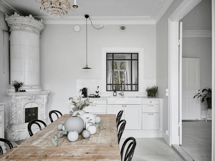 comedor con mesa grande rectangular de madera rústica, sillas negras, combinación de estilo lujoso y escandinavo, chimenea antigua, lámpara de araña, bombilla colgante, lavabo con espejo