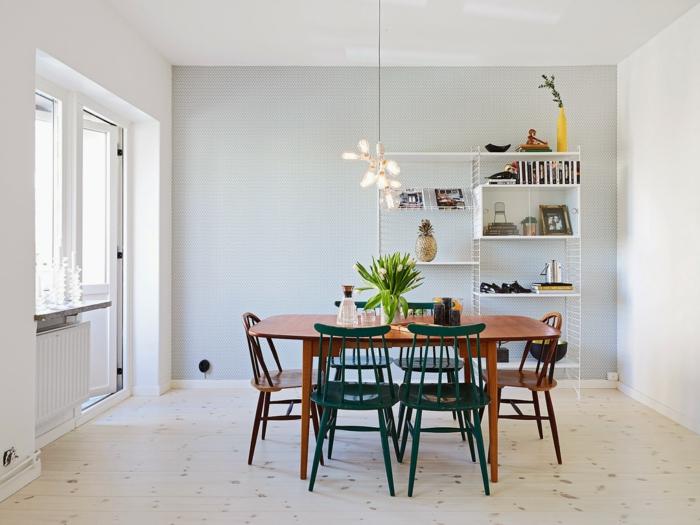 muebles estilo nordico, comedor con pocos muebles, mesa de madera, sillas en marrón y verde, estantería blanca alta de metal, lámpara colgante, suelo con tarima, ventanas sin cortinas