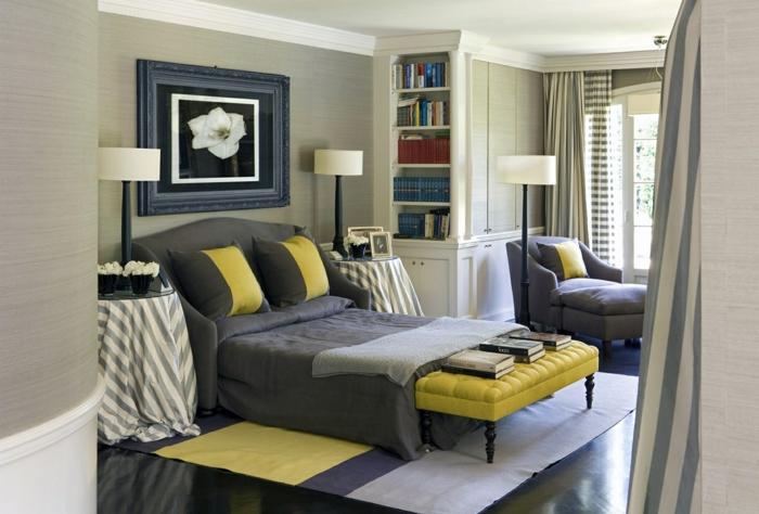 dormitorio grande moderno, habitacion gris, pie de cama de cuero en capitoné, cuadro con lirio, tapete en suelo lamiando, sillón y ventana grande