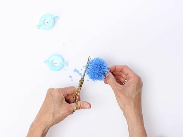 alfombra de pompones paso a paso, como hacer un precioso pompon azul hecho de lana, recortar el hilo con tijeras