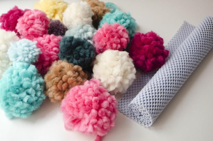 ejemplo de una alfombra de pompones hecha a mano, preciosos pompones DIY en diferentes colores y estera con agujeros