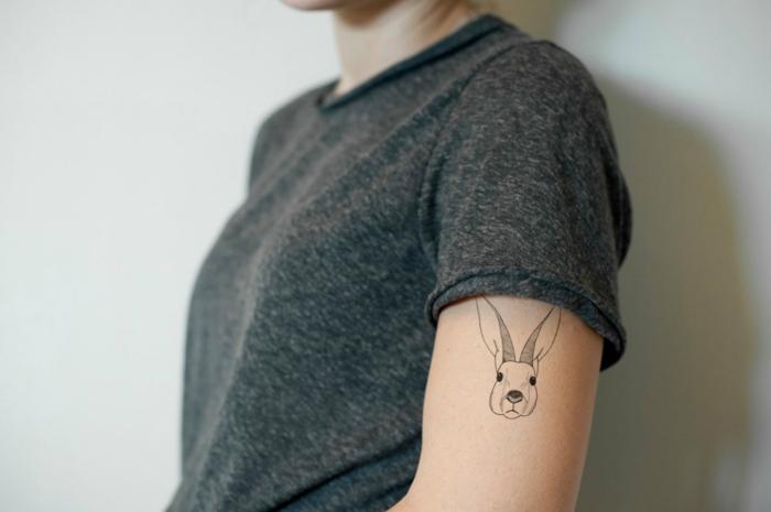 tatuajes simbolicos, mujer con camiseta gris, tatuaje en el brazo, cabeza de conejo, inspiracion alisa en el pais de maravillas