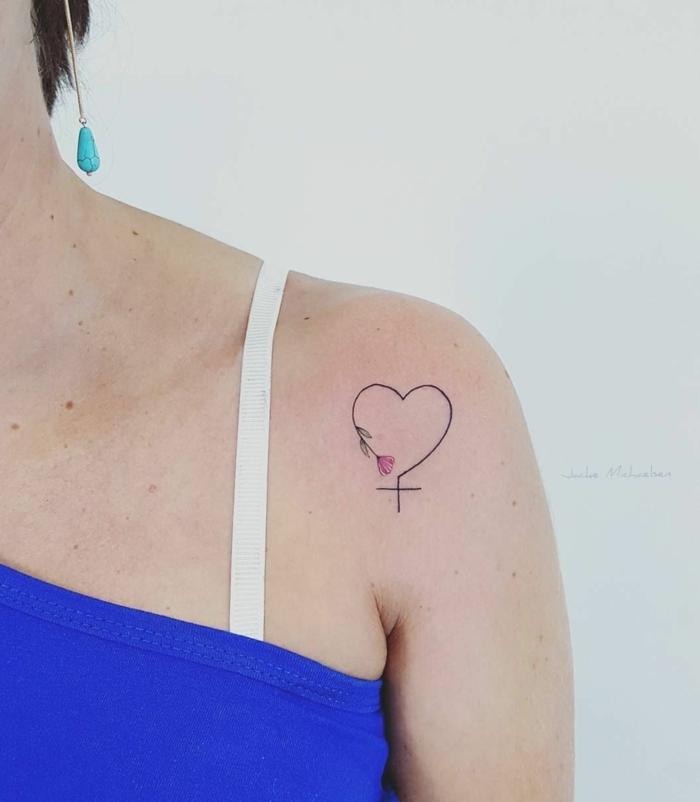 tatuajes con significado, combinacion de tres simbolos, corazon, cruz y amapola, tatuaje hombro mujer, blusa azul, correa blanca
