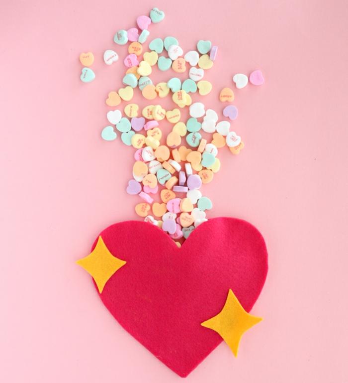 bolsa hecha a mano llena de caramelos en forma de corazón, manualidades de fieltro para regalar en el día de los enamorados