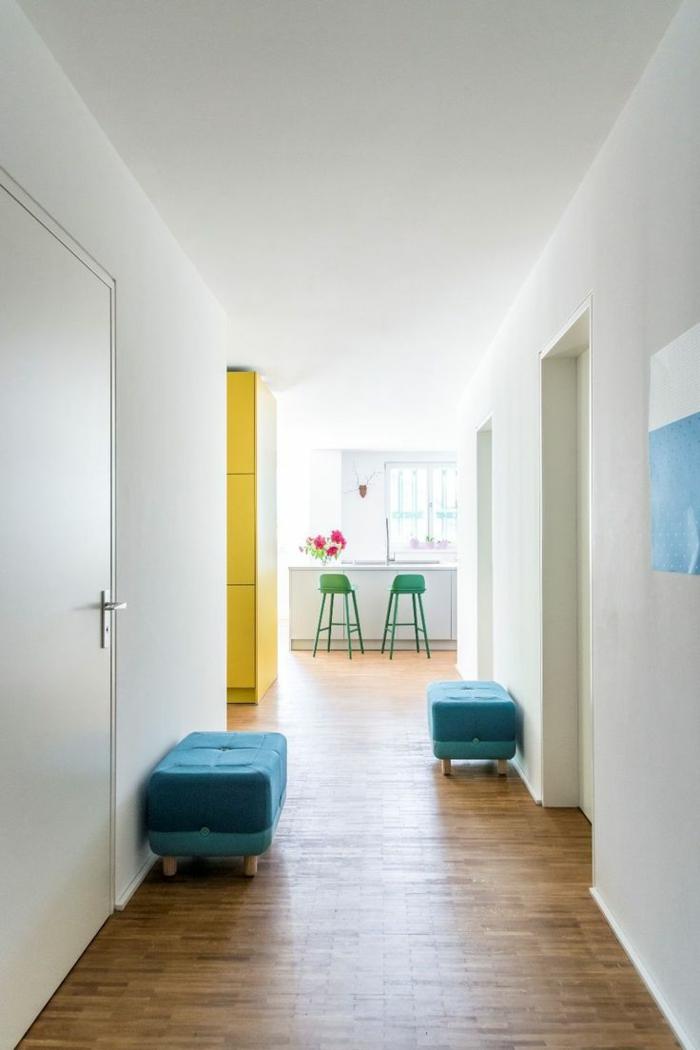 recibidor pequeño y alargado decorado de dos taburetes tapizadas en terciopelo color azul, suelo de parquet y paredes en blanco