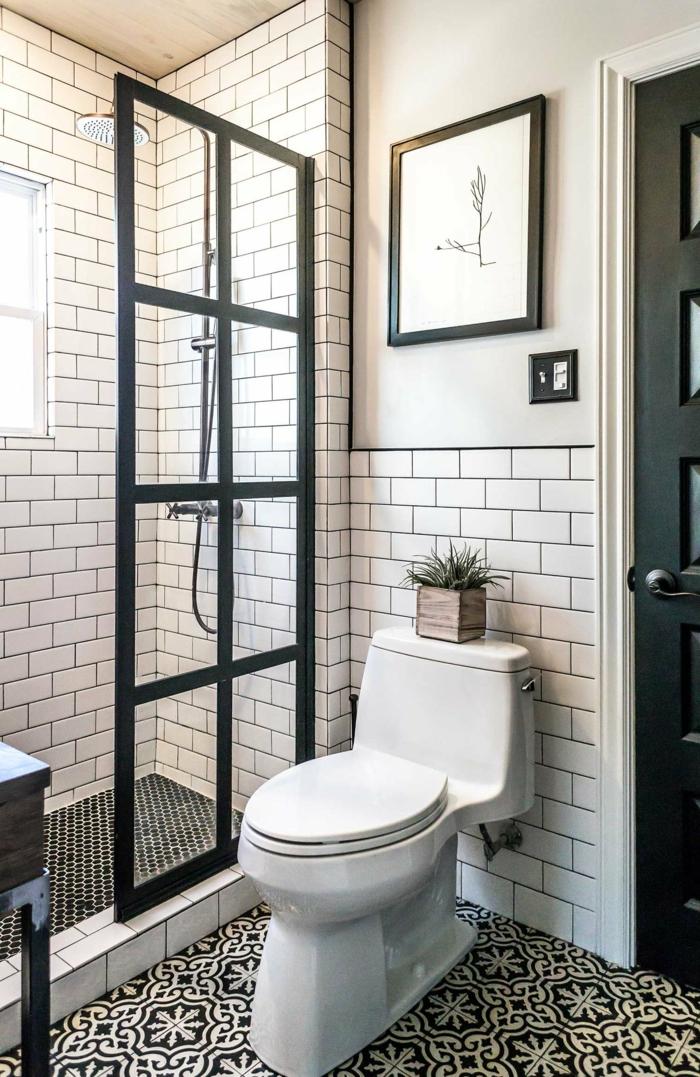 ducha de obra con mampara de vidrio en marco negro, decoracion moderna, cuadro sobre el vñater, ventana pequeña, baños pequeños con ducha
