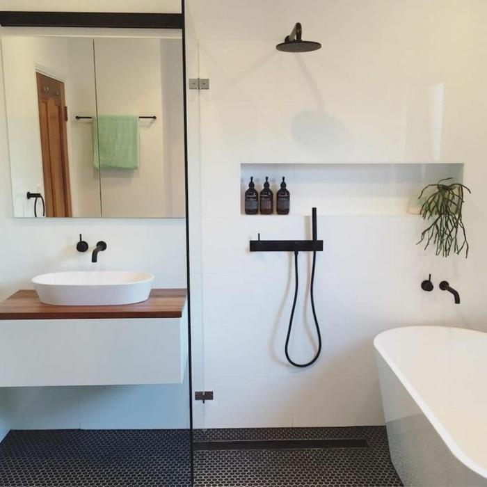 baño pequeño con ducha y bañera, decoración nordica en blanco y negro, lavabo con encimera de madera, pared con nicho, baños pequeños con ducha