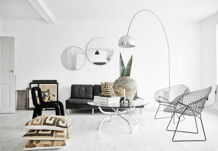 blanco y negro, decoracion nordica salon, suelo con tarima, mesa redonda de vidrio con patas de metal, macetero grande, espejos redondos, cuadros apoyados en el suelo, sillas con huecos, luz natural