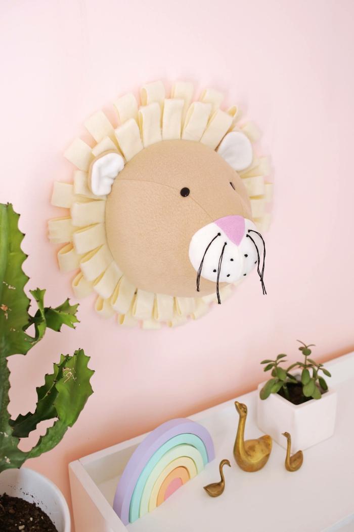 manualidades faciles para vender paso a paso, decorar las paredes con una cabeza de león hecha de tela en color beige, ojos y bigotes de hilo negro