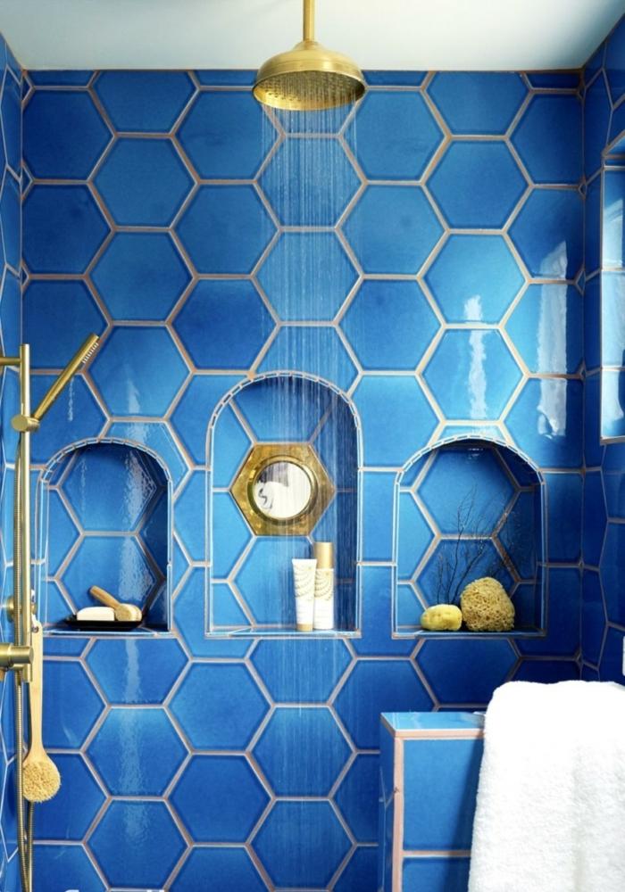 decoración original de baños en azul royal con baldosas hexagonales, nichos en la pared, ducha con efecto de lluvia, metal color dorado, baños modernos