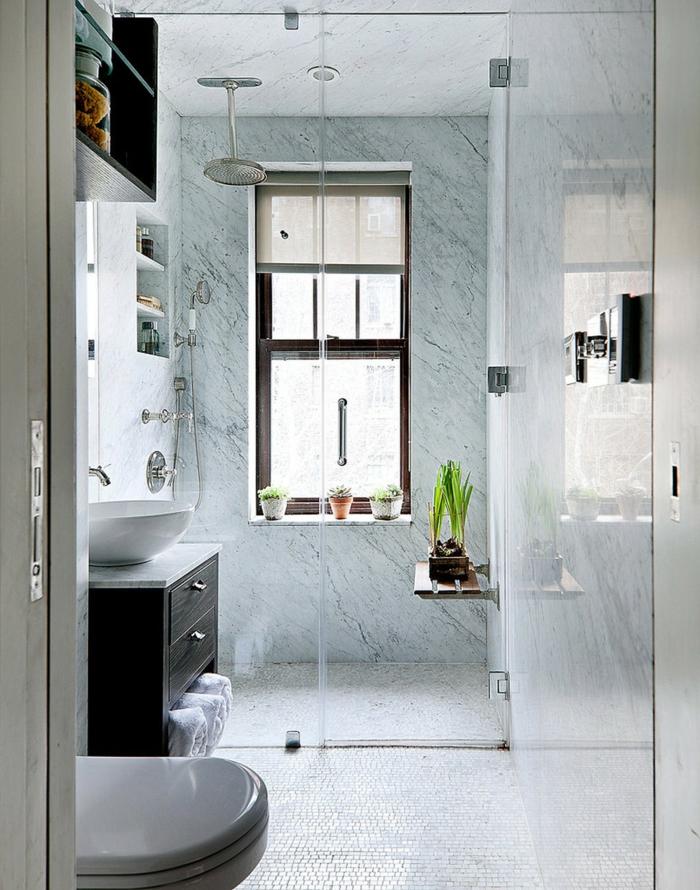 baño con ducha y ventana grande decorada con siemprevivas, paredes de mármol, suelo de mosaico, ducha efecto lluvia, baños modernos