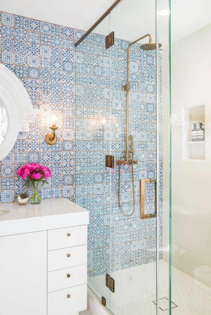baño en estilo ecléctico, pared con azulejos en azul, ducha con puerta de vidrio y asa dorada, espejo redondo, mueble lavabo grande con flores ciclamen
