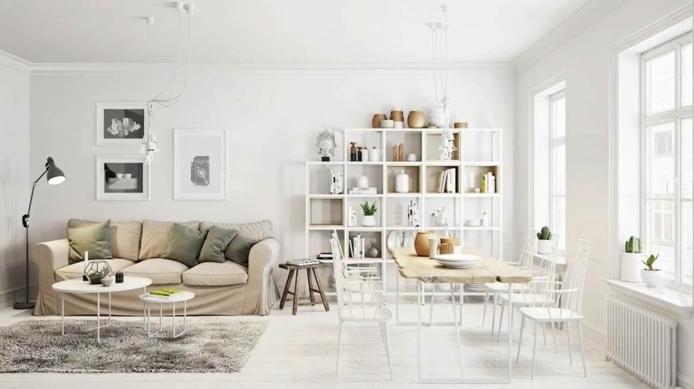 decoracion nordica, salón comedor, estantería de madera blanca con libros y jarrones, mesa de madera natural con sillas blancas, sofá beige con cojines color oliva, tapete peludo gris, ventanas grandes