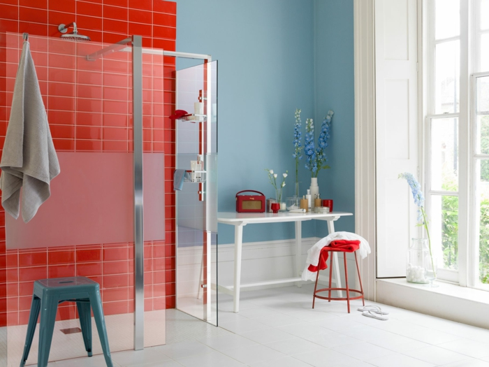 baño pequeño moderno con mucha luz natural, pared en azul, mesa de madera blanca, baldosas rojas, cuartos de baño pequeños, ducha de obra, mampara de vidrio