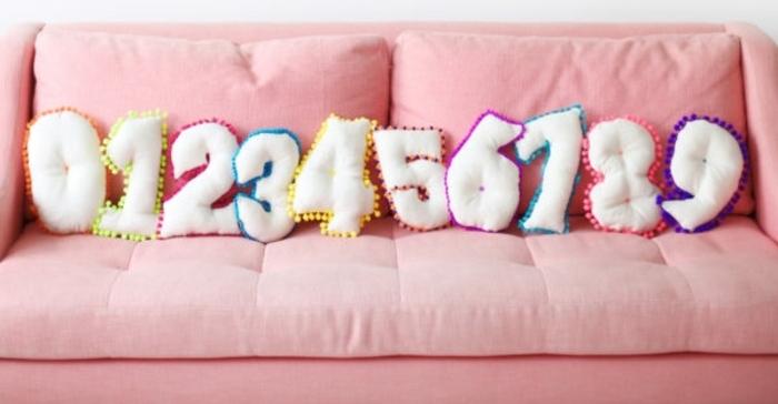 precioso sofá en capitoné color rosa decorado de cojines decorativos DIY en forma de los números de cero a nueve, manualidades con fieltro para regalar