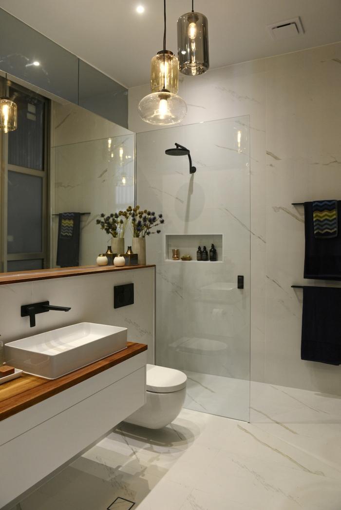 baño moderno pequeño, decoracion con marmol y lamparas colgantes, ducha de obra con nichos en la pared, espejo grande, baños modernos