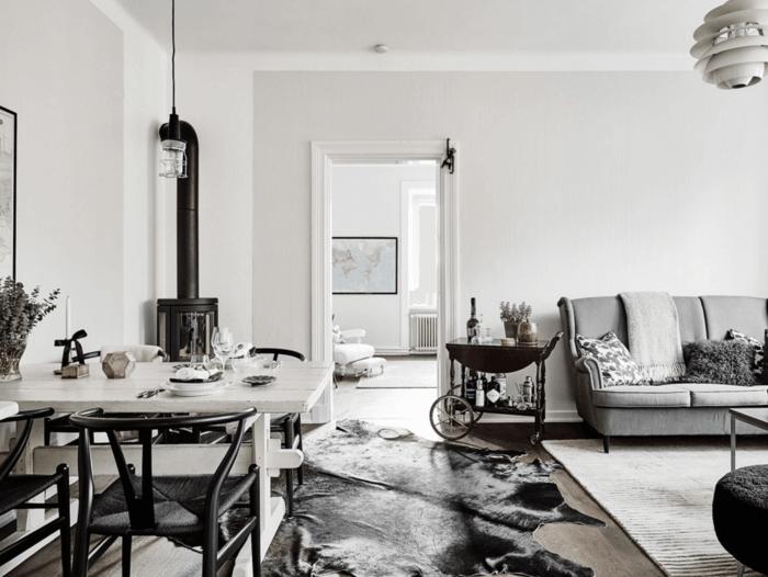 decoración en blanco y negro, salon nordico on chimenea y alfombra piel de vaca, sofá gris, mesa para cuatro, lámpara colgante
