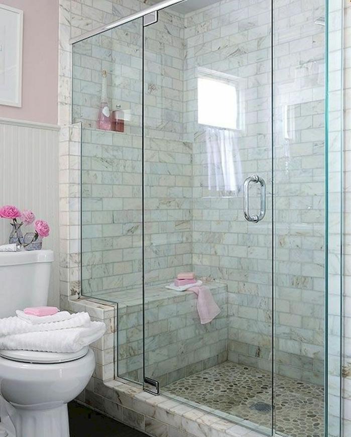 ideas baños pequeños, decoracion en gris y rosado, ducha de obra con banco, estilo spa, suelo con piedritas, puerta de vidrio