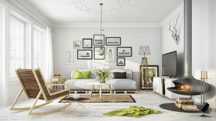 salón en blanco con acentos de madera y verde maznana, estilo nordico, chimenea colgante encendida, pared con cuadros, tapete de mimbre, sillón de madera, imitación cabeza de ciervo, ventanas grandes