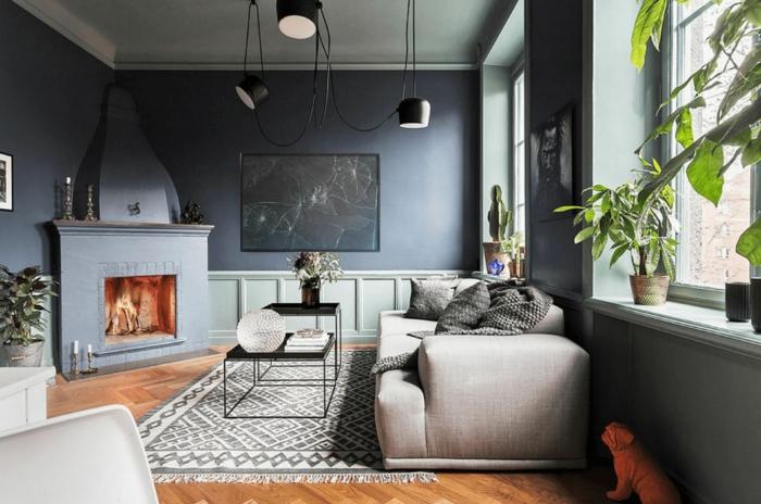paredes en azul grisáceo, chiemnea de obra, estilo nórdico, salón con aprquet y tapete, sofá beige con cojines, lá,mparas colgantes negras, ventanas grandes y plantas verdes