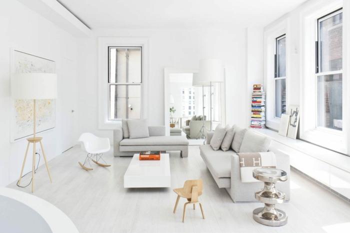 salon en blanco, estilo nordico, espacio grande, pared con mapa, sillas para niños, espejo enmarcado grande, pila de libros, sofá y mesa baja laminada