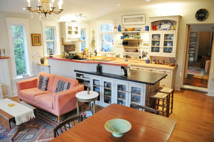 ambiente de encanto de pequeño tamaño, cocina abierta a la sala de estar, sofá acogedora en color salmón, candelabro vintage