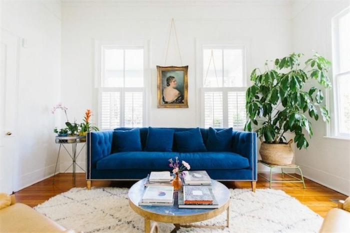 sofá con terciopelo azul, decoracion nordica, mesita baja redonda con revistas, árbol decorativo, retrato de mujer de espaldas estilo clásico, tapete blanco en rombos