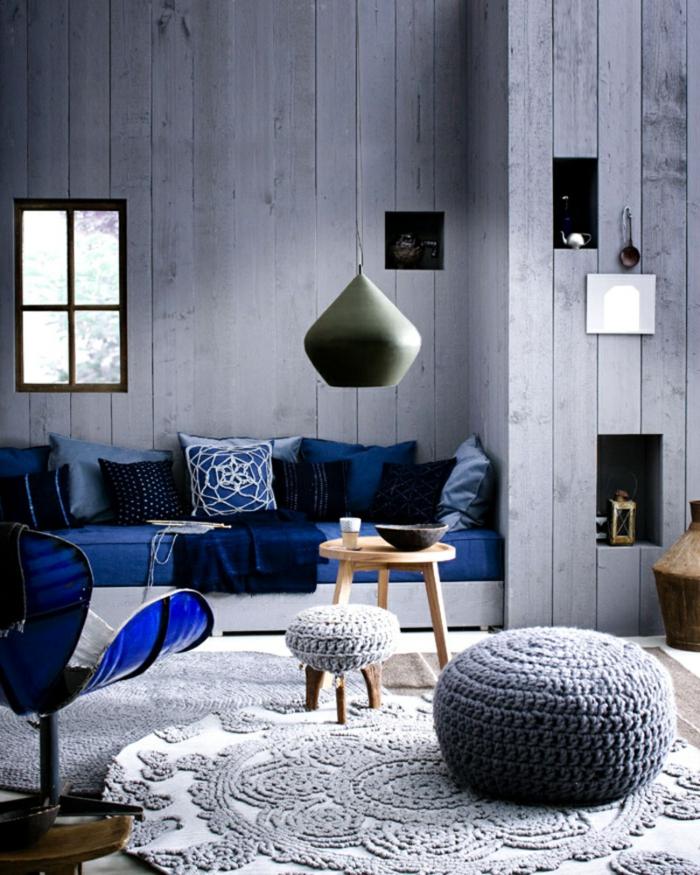 combinación de estilo rústico y escandinavo, salón en azul, paredes de listones con nichos decorativos, decoracion nordica, ventana pequeña, tapete de ganchillo, mini mesa redonda de madera