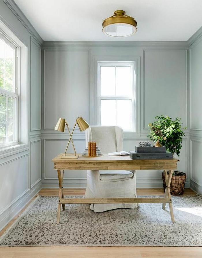 despacho pequeño con escritorio de amdera y sillon tapizado, paredes grises con moldura, luz natural, alfombra, planta verde, como decorar una habitacion
